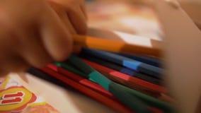 Λίγο μωρό δίνει κοντά επάνω παίρνει τα χρωματισμένα μολύβια σε σε αργή κίνηση απόθεμα βίντεο
