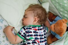 Λίγο μωρό είναι κοιμισμένο στο κρεβάτι του Εγχώριες επιπλώσεις Με το παιδί ένα παιχνίδι αντέχει στοκ φωτογραφία με δικαίωμα ελεύθερης χρήσης