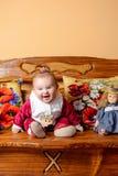 Λίγο μωρό με μια ουρά κάθεται σε έναν καναπέ με τα κεντημένα μαξιλάρια και τα παιχνίδια στοκ φωτογραφίες με δικαίωμα ελεύθερης χρήσης