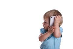 Λίγο μωρό παίζει με το κινητό τηλέφωνο, που απομονώνεται σε ένα λευκό Στοκ φωτογραφίες με δικαίωμα ελεύθερης χρήσης