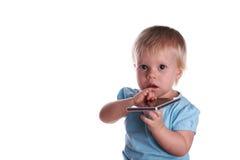 Λίγο μωρό παίζει με το κινητό τηλέφωνο, που απομονώνεται σε ένα λευκό Στοκ εικόνα με δικαίωμα ελεύθερης χρήσης