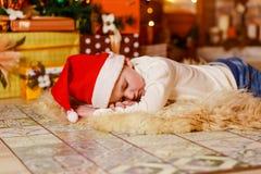 Λίγο μωρό που βρίσκεται σε ένα χνουδωτό κάλυμμα κάτω από το χριστουγεννιάτικο δέντρο στοκ εικόνες με δικαίωμα ελεύθερης χρήσης