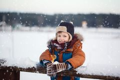 Λίγο μωρό που παίζει και που τρώει γλυκό cockerel στη χειμερινή ημέρα Παιχνίδι παιδιών στο χιονώδες δάσος στοκ εικόνες με δικαίωμα ελεύθερης χρήσης