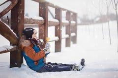 Λίγο μωρό που παίζει και που τρώει γλυκό cockerel στη χειμερινή ημέρα Παιχνίδι παιδιών στο χιονώδες δάσος στοκ φωτογραφίες