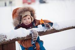 Λίγο μωρό που παίζει και που τρώει γλυκό cockerel στη χειμερινή ημέρα στοκ εικόνα