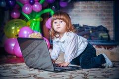 Λίγο μωρό που παίζει με το lap-top Στοκ Φωτογραφίες