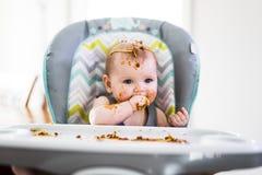 Λίγο μωρό που τρώει το γεύμα της και που κάνει να βρωμίσει Στοκ Εικόνες