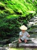 Λίγο μωρό που φορά παιχνίδια μιας τα παραδοσιακά yukata συνήθειας με τα δασικά φύλλα καθμένος πέρα από τα βήματα πετρών του ναού  Στοκ Φωτογραφίες