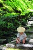 Λίγο μωρό που φορά παιχνίδια μιας τα παραδοσιακά yukata συνήθειας με τα δασικά φύλλα καθμένος πέρα από τα βήματα πετρών του ναού  Στοκ φωτογραφία με δικαίωμα ελεύθερης χρήσης
