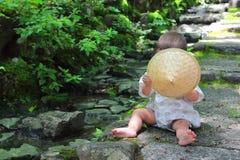 Λίγο μωρό που φορά παιχνίδια μιας τα παραδοσιακά yukata συνήθειας με τα δασικά φύλλα καθμένος πέρα από τα βήματα πετρών του ναού  Στοκ Εικόνα