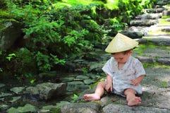 Λίγο μωρό που φορά παιχνίδια μιας τα παραδοσιακά yukata συνήθειας με τα δασικά φύλλα καθμένος πέρα από τα βήματα πετρών του ναού  Στοκ Φωτογραφία