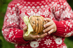 Λίγο μωρό στα μπισκότα εκμετάλλευσης πουλόβερ Χριστουγέννων με την κορδέλλα Στοκ φωτογραφία με δικαίωμα ελεύθερης χρήσης