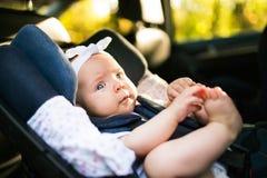 Λίγο μωρό στερέωσε με τη ζώνη ασφάλειας στο κάθισμα αυτοκινήτων ασφάλειας Στοκ Εικόνα