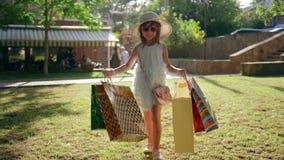 Λίγο μόδα-κορίτσι με τις τσάντες αγορών μετά από να επισκεφτεί τις ακριβές μπουτίκ περπατά στο χορτοτάπητα και χαμογελά απόθεμα βίντεο