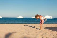 Λίγο νέο κορίτσι που ψάχνει στην άμμο θάλασσας Στοκ Φωτογραφία