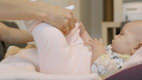 Λίγο νήπιο που βρίσκεται στη μεταφορά μωρών στο σπίτι και που ντύνεται απόθεμα βίντεο
