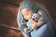 Λίγο νεογέννητο αγοράκι, που κοιμάται στο καλάθι, που κρατά το παιχνίδι Στοκ εικόνα με δικαίωμα ελεύθερης χρήσης