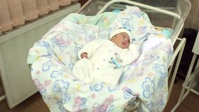 Λίγο νεογέννητο μωρό που βρίσκεται σε ένα λίκνο στο νοσοκομείο απόθεμα βίντεο
