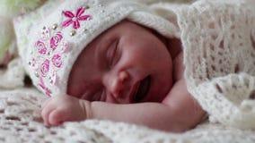 Λίγο νεογέννητο μωρό στους ύπνους και τους μορφασμούς καπέλων στο χνουδωτό κάλυμμα απόθεμα βίντεο