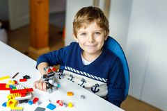 Λίγο ξανθό αγόρι παιδιών που παίζει με τα μέρη των ζωηρόχρωμων πλαστικών φραγμών στοκ φωτογραφία με δικαίωμα ελεύθερης χρήσης