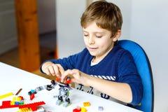 Λίγο ξανθό αγόρι παιδιών που παίζει με τα μέρη των ζωηρόχρωμων πλαστικών φραγμών Στοκ εικόνα με δικαίωμα ελεύθερης χρήσης