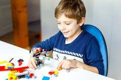 Λίγο ξανθό αγόρι παιδιών που παίζει με τα μέρη των ζωηρόχρωμων πλαστικών φραγμών Στοκ φωτογραφίες με δικαίωμα ελεύθερης χρήσης