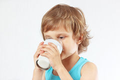 Λίγο ξανθό αγόρι που πίνει το φρέσκο γάλα στο άσπρο υπόβαθρο Στοκ φωτογραφία με δικαίωμα ελεύθερης χρήσης