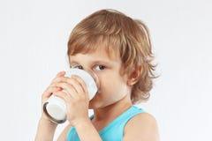 Λίγο ξανθό αγόρι που πίνει φρέσκο kefir στο άσπρο υπόβαθρο Στοκ εικόνες με δικαίωμα ελεύθερης χρήσης