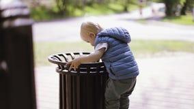 Λίγο ξανθό αγόρι που παίζει με τα απορρίμματα στο πάρκο απόθεμα βίντεο