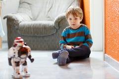 Λίγο ξανθό αγόρι που παίζει με το παιχνίδι ρομπότ στο σπίτι, εσωτερικό Στοκ εικόνα με δικαίωμα ελεύθερης χρήσης
