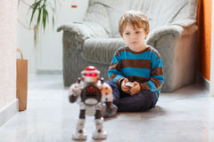 Λίγο ξανθό αγόρι που παίζει με το παιχνίδι ρομπότ στο σπίτι, εσωτερικό Στοκ Φωτογραφία