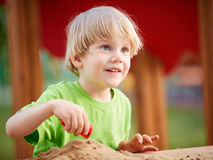 Λίγο ξανθό αγόρι που παίζει στην παιδική χαρά Στοκ Εικόνες