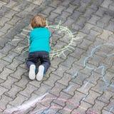 Λίγο ξανθό αγόρι που χρωματίζει με τις ζωηρόχρωμες κιμωλίες υπαίθρια Στοκ Εικόνες
