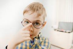 Λίγο ξανθό αγόρι στο πουκάμισο καρό διόγκωσε έξω τα μεγάλα μπλε μάτια του στοκ φωτογραφία με δικαίωμα ελεύθερης χρήσης