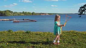 Λίγο ξανθό κορίτσι διογκώνει τις μεγάλες φυσαλίδες σαπουνιών ενάντια στο σκηνικό της παραλίας απόθεμα βίντεο