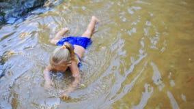 Λίγο ξανθό κορίτσι κολυμπά στο ρηχό αμμώδες κατώτατο σημείο λιμνών απόθεμα βίντεο