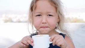 Λίγο ξανθό κορίτσι πίνει το κακάο από το άσπρο φλυτζάνι φιλμ μικρού μήκους