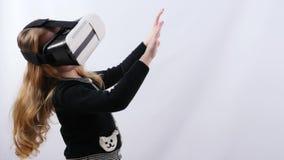 Λίγο ξανθό κορίτσι παίζει το παιχνίδι εικονικής πραγματικότητας στο στούντιο φιλμ μικρού μήκους
