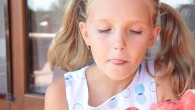 Λίγο ξανθό κορίτσι που τρώει το καλοκαίρι καρπουζιών απολαμβάνει υπαίθρια φιλμ μικρού μήκους