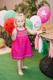Λίγο ξανθό κορίτσι σε ένα ρόδινο φόρεμα που στέκεται στο κατώφλι με τα ζωηρόχρωμα μπαλόνια στοκ φωτογραφίες