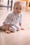 Λίγο ξανθό κορίτσι στη ριγωτή συνεδρίαση πουκάμισων στο ξύλινο πάτωμα Στοκ φωτογραφία με δικαίωμα ελεύθερης χρήσης