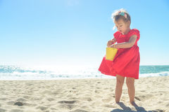 Λίγο ξανθό κορίτσι στο κόκκινο φόρεμα στην παραλία Στοκ εικόνα με δικαίωμα ελεύθερης χρήσης