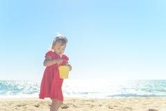 Λίγο ξανθό κορίτσι στο κόκκινο φόρεμα στην παραλία Στοκ εικόνες με δικαίωμα ελεύθερης χρήσης