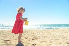 Λίγο ξανθό κορίτσι στο κόκκινο φόρεμα στην παραλία Στοκ Φωτογραφίες
