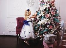 Λίγο ξανθό κορίτσι στο όμορφο φόρεμα που διακοσμεί το χριστουγεννιάτικο δέντρο στο σπίτι Στοκ φωτογραφία με δικαίωμα ελεύθερης χρήσης