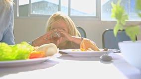 Λίγο ξανθό κορίτσι τρώει το κοτόπουλο κοντά στη μητέρα στον πίνακα απόθεμα βίντεο