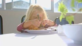 Λίγο ξανθό κορίτσι τρώει το κοτόπουλο με το μεγάλο κουτάλι στον πίνακα φιλμ μικρού μήκους