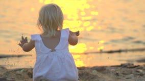 Λίγο παιδί κάθεται στην παραλία κατά τη διάρκεια του όμορφου χρόνου διακοπών ηλιοβασιλέματος ευτυχούς σε σε αργή κίνηση Παιδί που φιλμ μικρού μήκους