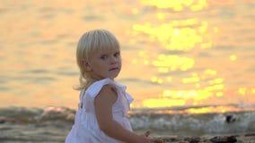 Λίγο παιδί κάθεται στην παραλία κατά τη διάρκεια του όμορφου χρόνου διακοπών ηλιοβασιλέματος ευτυχούς σε σε αργή κίνηση Παιδί που απόθεμα βίντεο