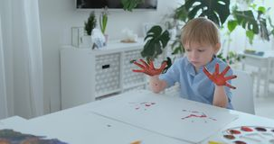 Λίγο παιδί με τα χέρια χρωμάτισε στα ζωηρόχρωμα χρώματα έτοιμα για τις τυπωμένες ύλες χεριών απόθεμα βίντεο